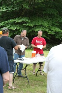 Pastors Ed and Jim serving communion by the river